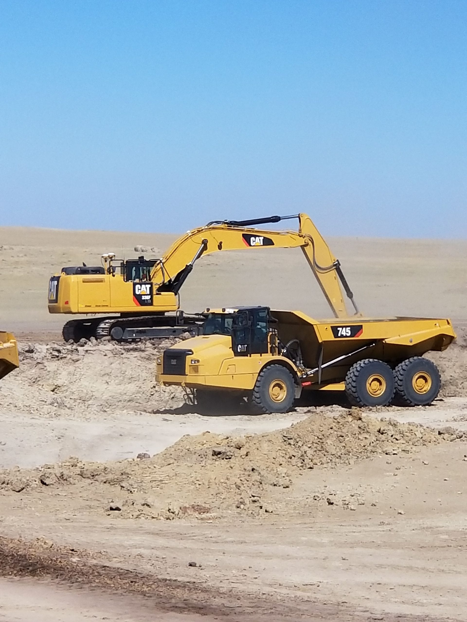 Excavator and articulated truck